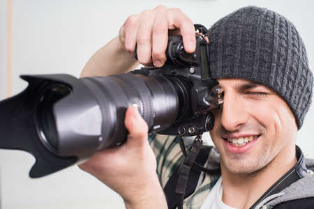 lens unit: Young smiling photographer is using professional camera on gray background.