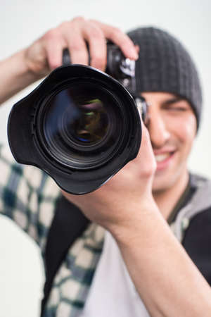 lens unit: Young smiling photographer is using professional camera on gray background. Close-up.