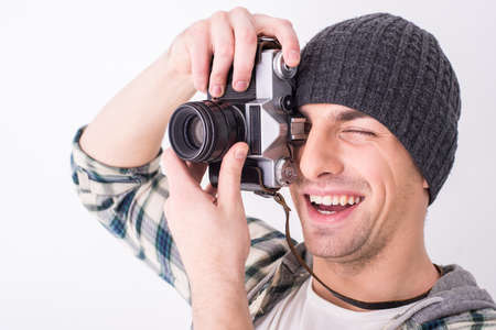 lens unit: Young smiling photographer with camera on the gray background.