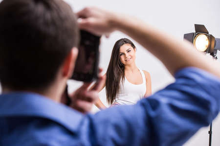 professionally: Photographer at work with model in the professionally equipped studio.