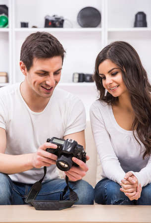 Young couple are looking at photographs on camera. photo