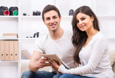 Young couple are using pc tablet to looking at photographs and looking at the camera. photo