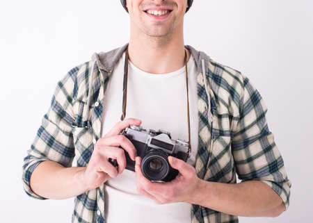 Young smiling photographer with camera on the gray background. photo