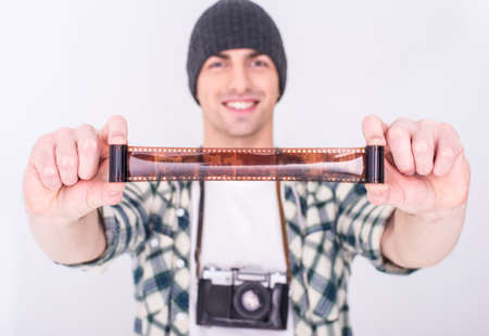 Young smiling man, photographer is looking at the film on the gray background. photo