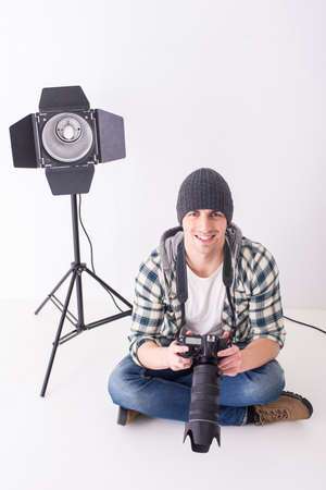 lens unit: Young smiling photographer with camera in professionally equipped studio is sitting on the floor.