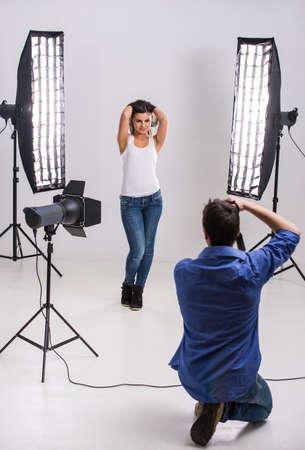 hombre disparando: Fot�grafo en el trabajo con el modelo en el estudio con equipo profesional.