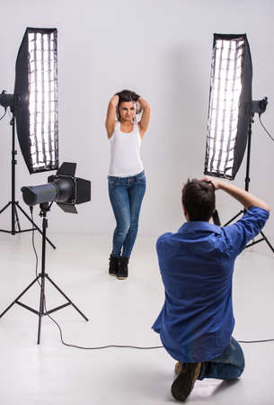 Photographer at work with model in the professionally equipped studio.