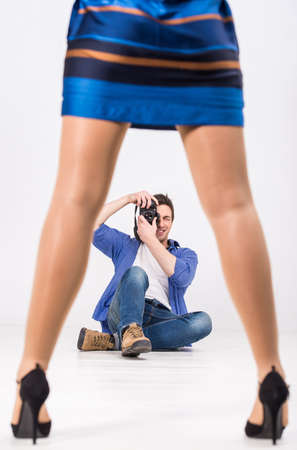professionally: Young photographer with camera in professionally equipped studio. Stock Photo