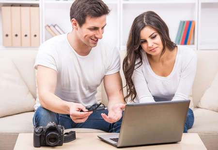 Young couple are looking at photographs on laptop. photo