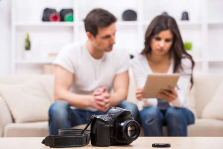 Young couple are looking at photographs on pc tablet. Focus on camera on the table. photo