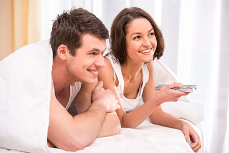 Young couple waking up and watching TV on the bed at home. photo