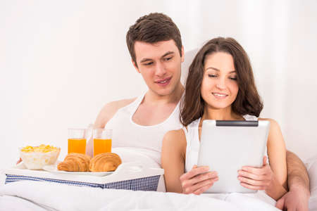 Smiling young couple having breakfast and using tablet in bed. photo