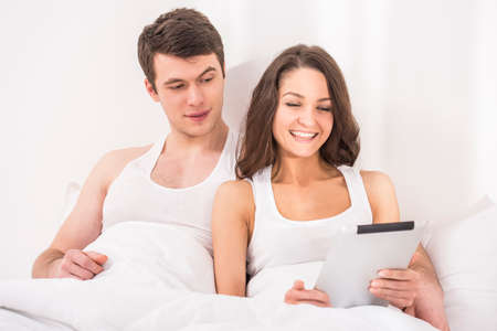 Smiling young couple using tablet in bed. photo