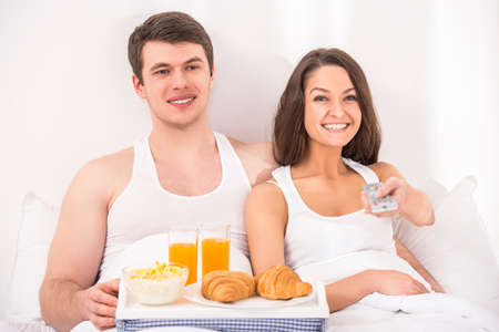 Smiling young couple having breakfast and watching TV in bed. photo