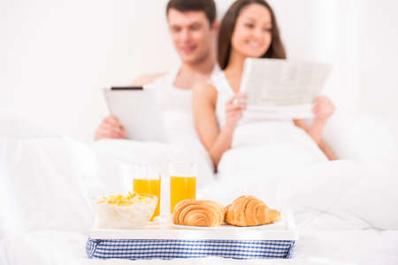 Smiling young couple having breakfast  in bed. photo
