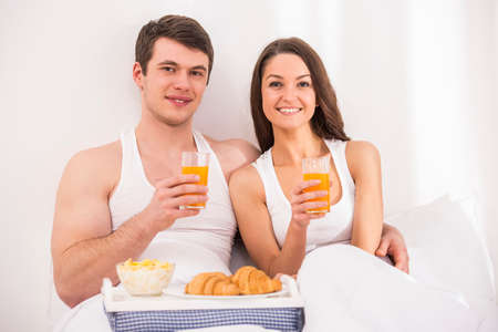 having breakfast: Smiling young couple having breakfast  in bed.