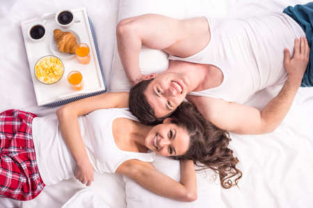 having breakfast: Top view. Smiling young couple having breakfast  in bed.