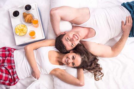 pareja comiendo: Vista superior. Sonriente joven pareja desayunando en la cama. Foto de archivo