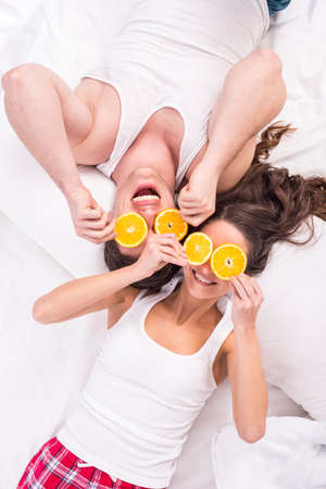 Top view. Young smiling couple lying on bed nad putting on eyes slices orange. photo