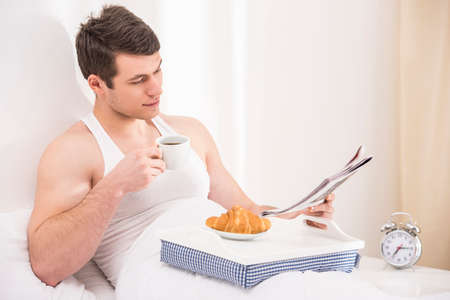 bedlinen: Good morning. Handsome young male  having breakfast in bed. Stock Photo