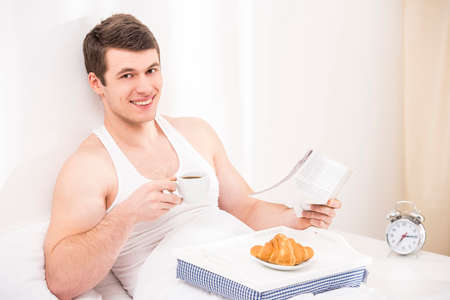 bedlinen: Good morning. Handsome young male  having breakfast in bed. Looking at camera.