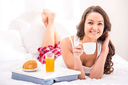 fmale: Good morning. Beauty young fmale having breakfast in bed. Looking at camera.
