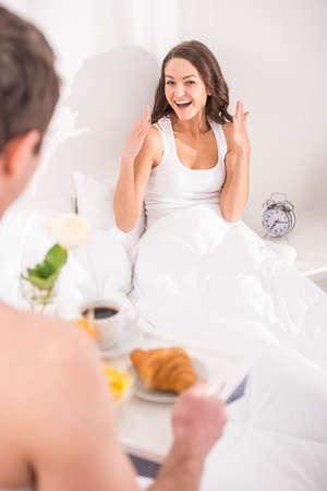 breakfast in bed: Husband bringing the breakfast to his wife in bed. Stock Photo