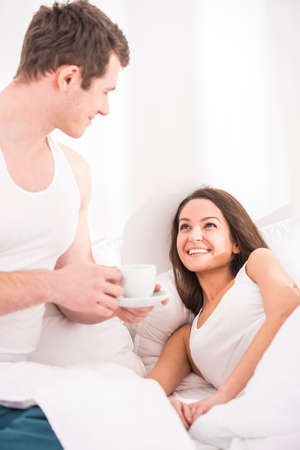 breakfast in bed: Husband bringing the coffee to his wife in bed. Stock Photo