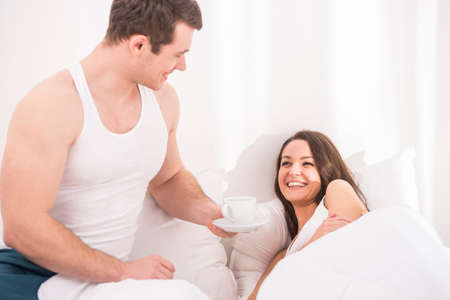 Husband bringing the coffee to his wife in bed. photo
