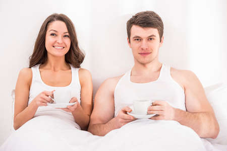 Smiling young couple having breakfast in bed. Looking at camera. photo