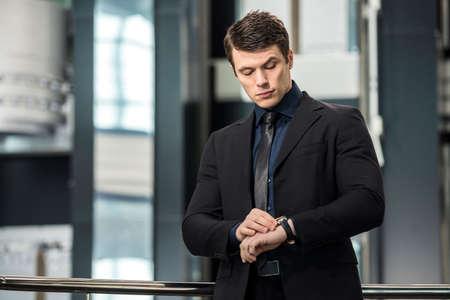 hombre fuerte: Hermoso joven empresario que mira en su reloj en la oficina moderna.