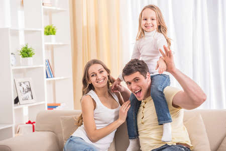 family portrait: Mother, father and daughter. Portrait of happy family sitting on sofa.