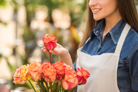 Dichtbij. Jonge vrouwelijke bloemist met een roos in de bloemenwinkel. Stockfoto