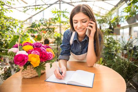 hablando por celular: Retrato de floristería mujer joven hablando por teléfono y haciendo notas en la tienda de flores. Foto de archivo