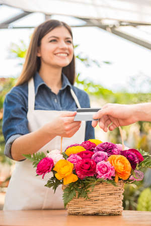 Close-up. Customer giving credit card to the seller florist. photo
