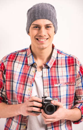 Portrait of handsome young man is holding vintage camera. photo