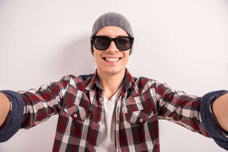 only one man: Handsome young man in sunglasses is making selfie and smiling while standing grey background.