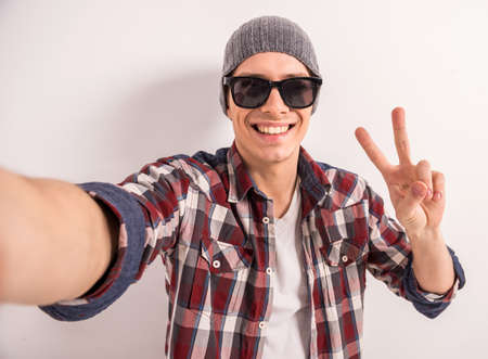 Handsome young man in sunglasses is making selfie and smiling while standing grey background.