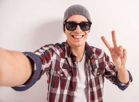 jovem: Homem novo considerável nos óculos de sol está fazendo selfie e sorrindo em pé fundo cinzento.