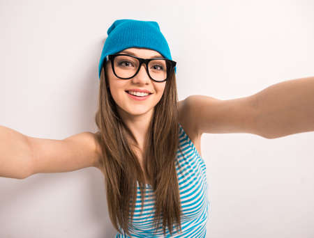 Beautiful young woman is making selfie standing against grey background.