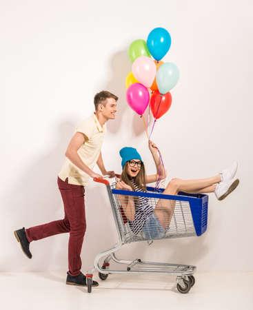 Retrato de joven pareja feliz se divierten. Niña sentada en el carrito de compras y mantenimiento de globos de colores en la mano. Individuo rodando carro. Foto de archivo - 39236350