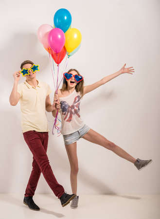 Cheerful young couple standing in funny glasses and holding colorful balloons. photo