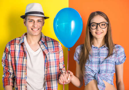 Beautiful couple having a fun together. Posing with blue balloon on colorful background. photo