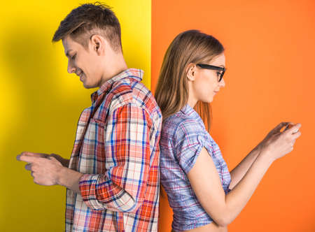phone isolated: Portrait of young couple standing back to each other and looking at the phone.