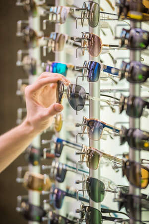 vision repair: Young man (only hands) at optician with glasses is looking for sunglasses. Stock Photo