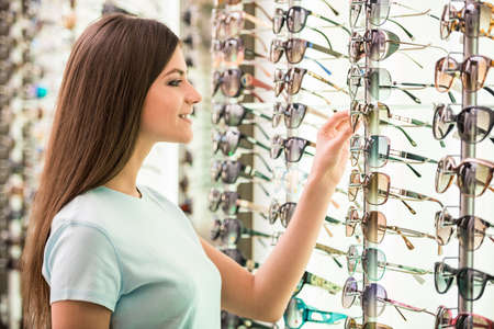 Young woman at optician with glasses is looking for sunglasses.