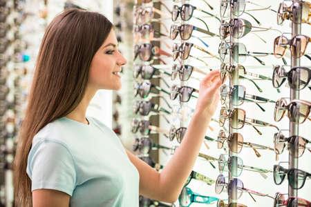Jeune femme au opticien avec des lunettes est à la recherche pour lunettes de soleil.
