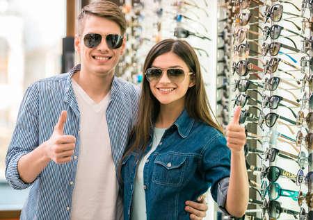 Jong paar bij opticien in de winkel, ze op zoek naar een bril. Stockfoto