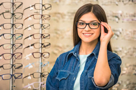 selecting: Portrait of happy young woman buying a new glasses at optician store. Stock Photo
