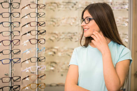 Young woman is choosing a glasses in optician store. photo
